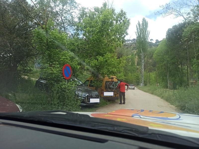 Coches aparcados en una zona expresamente prohibida como se observa por la señal vertical.